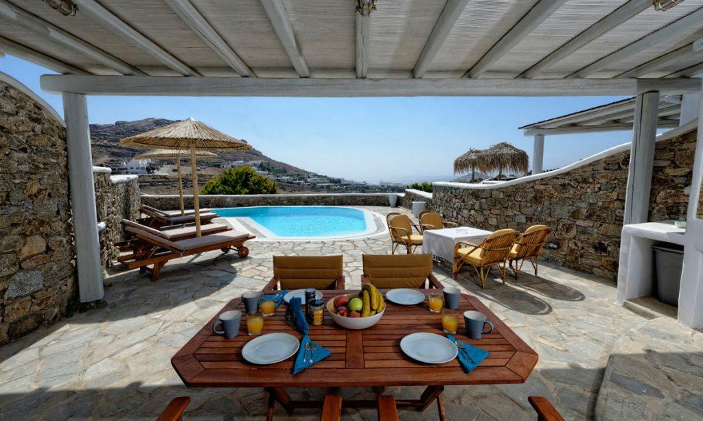 Villa-Valence-_10.jpg Kalafatis Mykonos, outdoor dining area, dining table, fruits, bowl, plates, napkins, forks, spoons, pool, chairs, climbers, umbrellas, sky