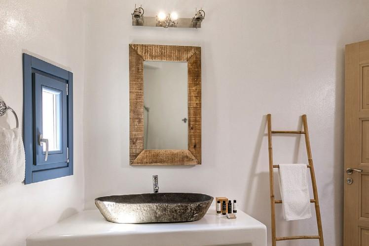 white wall bathroom with wooden mirror frame and ladder next to door