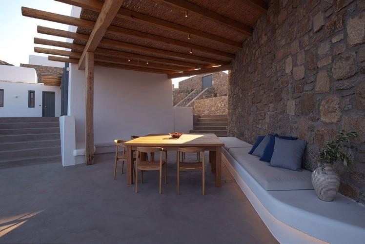 Villa_Jacob_09.jpg Kalafatis Mykonos Outdoor Dining area, bed, pillows, vase, flowers, table, chairs
