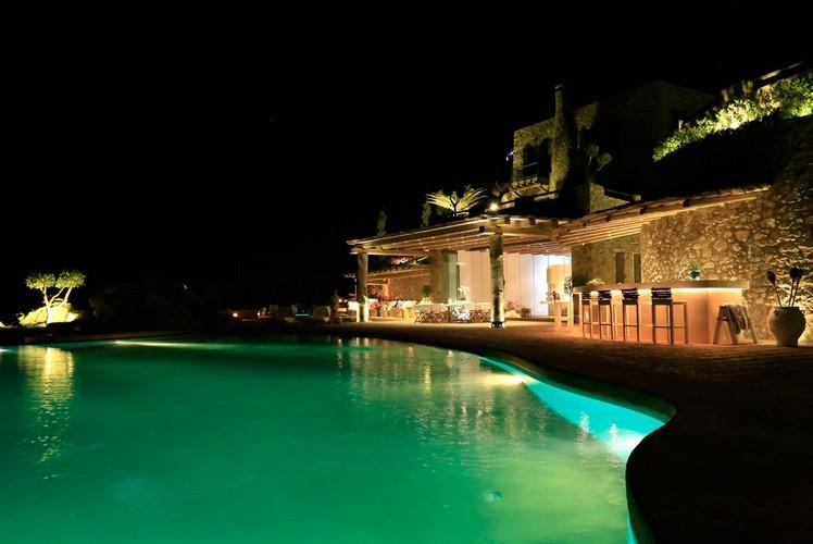 outdoor area with lighted bar and illuminated pool