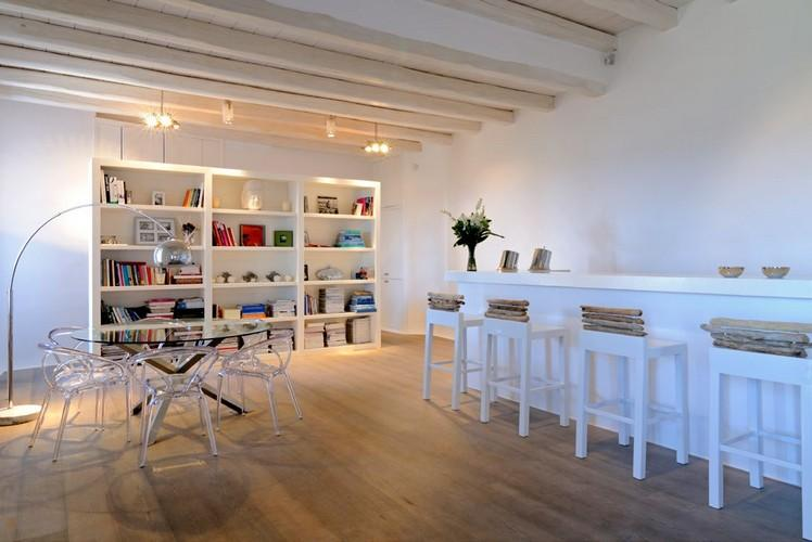 spacious area with book shelf and round glass table