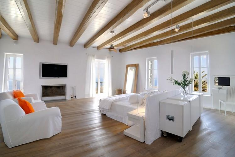 white designed bedroom with fire place and flat screen tv