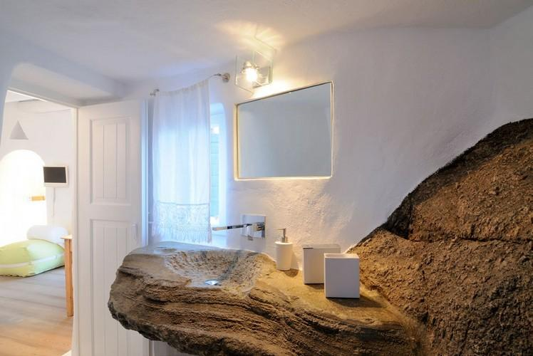 bathroom with mix of rocky and white walls with mirror