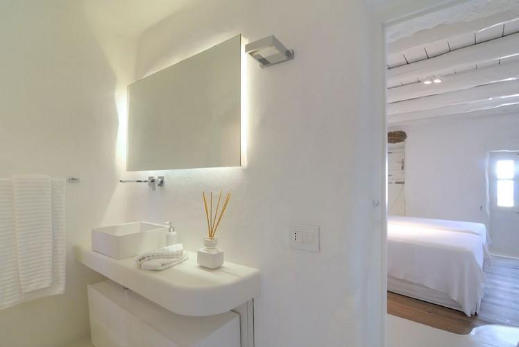 white wall bathroom with lighted mirror and soft towels