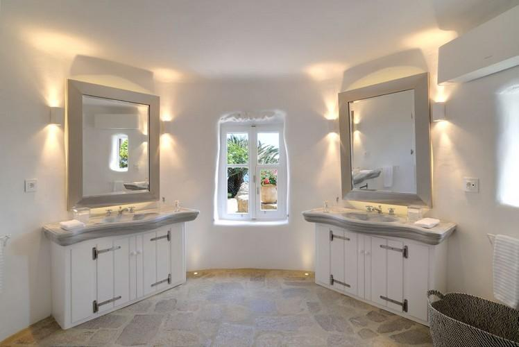 bathroom with illuminated mirror ceramic sinks and air condition