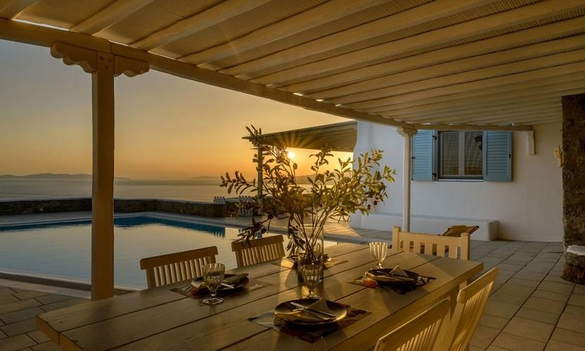 outdoor area with table and chairs for eating and enjoying sunset
