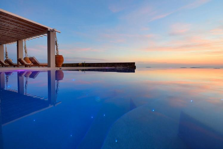 outdoor area with infinity pool and beautiful sunset view