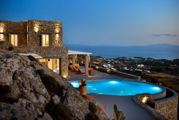 outdoor area with illuminated pool and stunning view