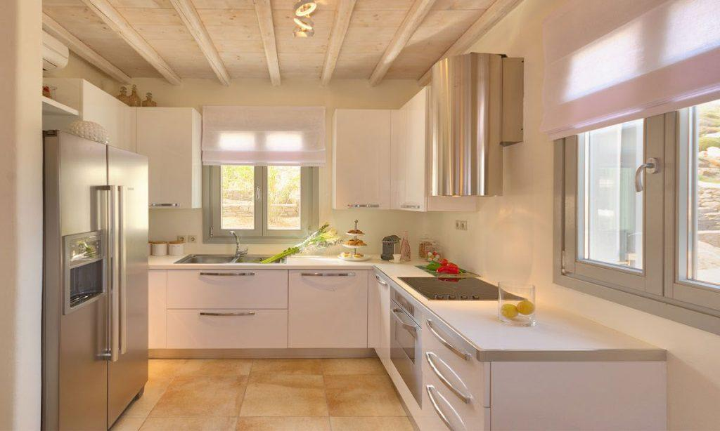 fully equipped kitchen with table and large windows