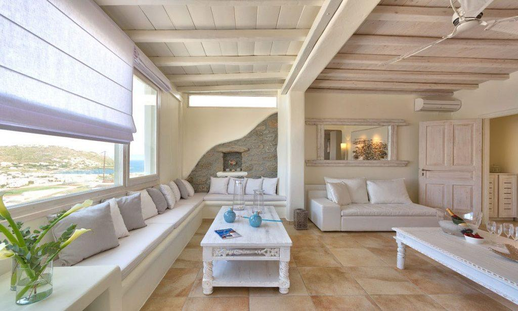 living room with windows assure view of mykonos city and sea