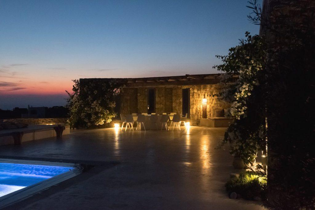 outdoor area at night with lamp and illuminated pool