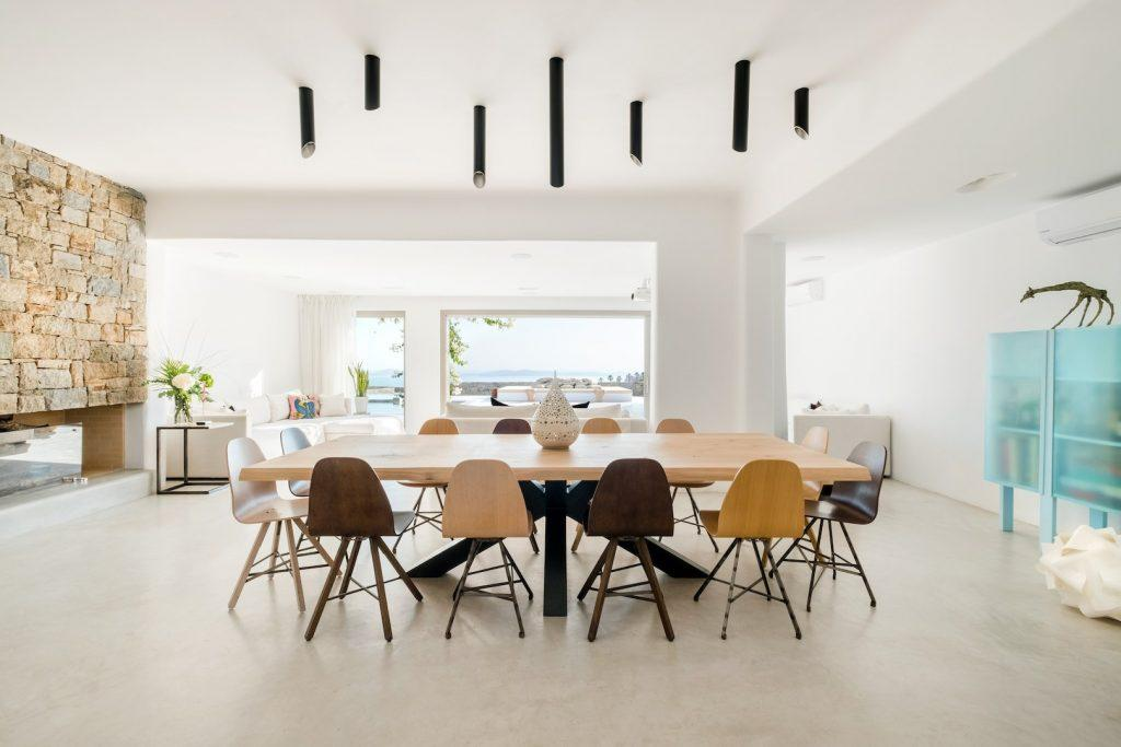 dining area with huge wooden table and random color chairs