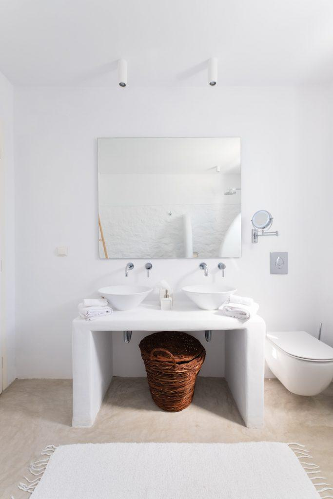 white wall bathroom with huge mirror and basket