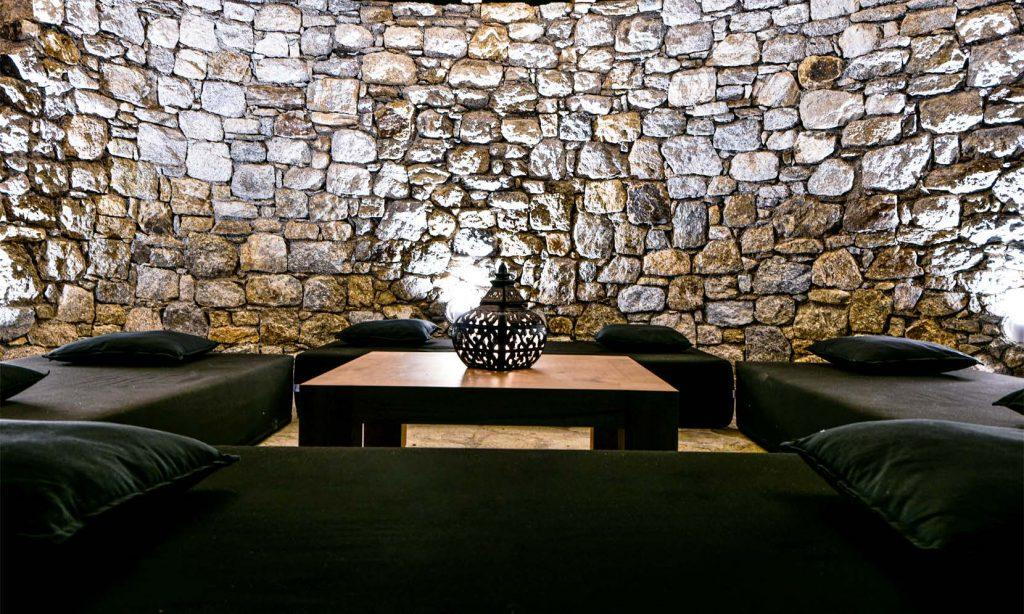 stone walls with lamps and wooden table
