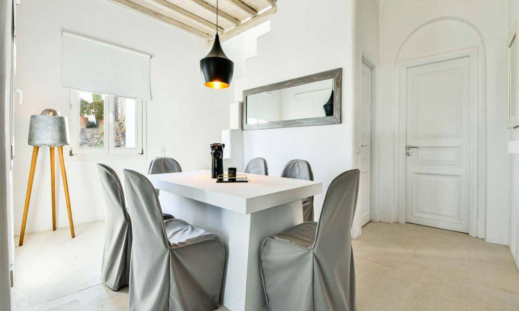 modern designed dining area with grey chair covers and mirror