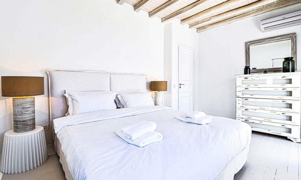 white wall bedroom with old wooden cabin and air condition