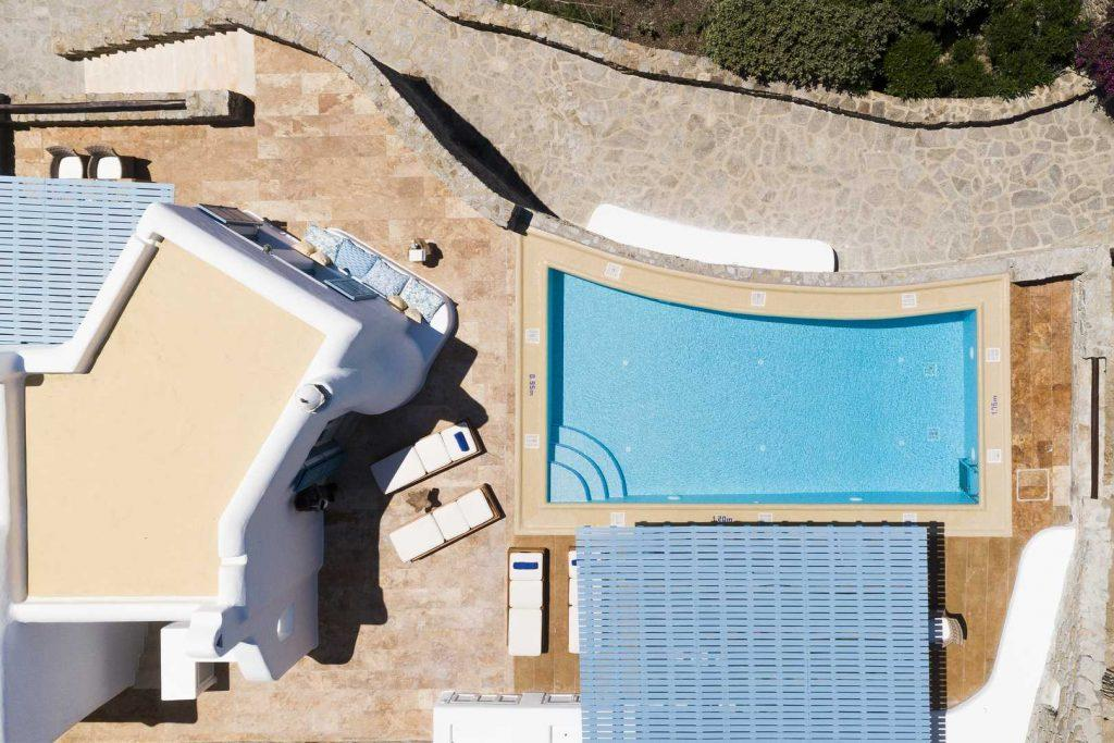 hawk eye view of outside area with swimming pool and stone walls