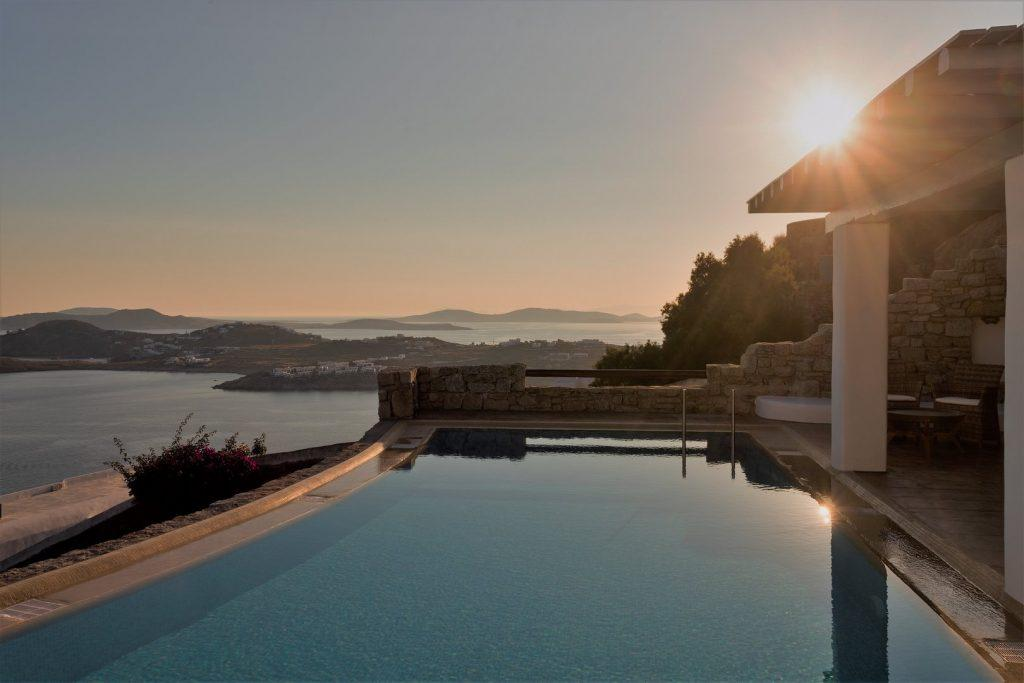 flawless sunset from infinity pool located at balcony with view of mykonos city and endless sea
