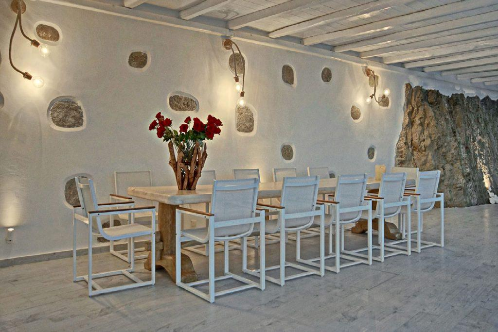 out door dining room with white walls and flowers