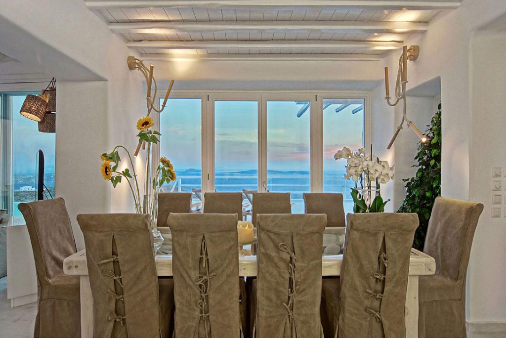 dining room with flowers, table, chairs and out door view