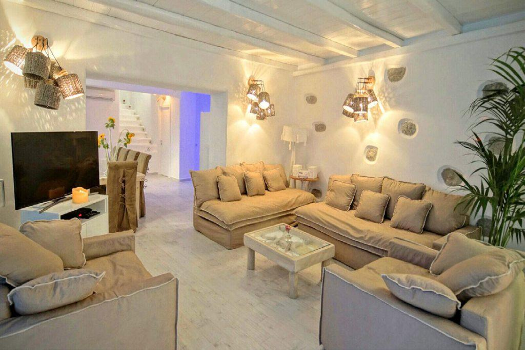 whitewashed living room with wall lamps that illuminate chairs and sofa