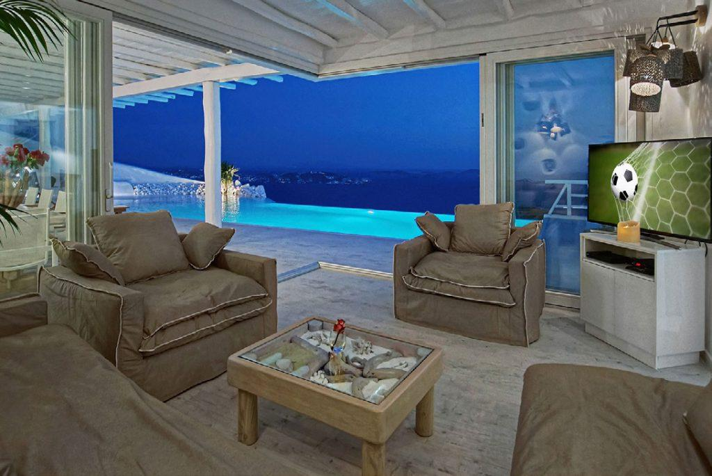 out door living room with view of sea and pool with wall lamps and white walls
