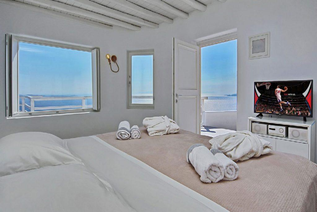 white bedroom with view of Kastro beach and balcony