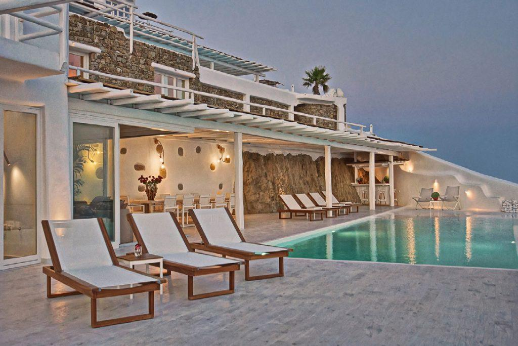 white stone wall villa with pool and sunbeds