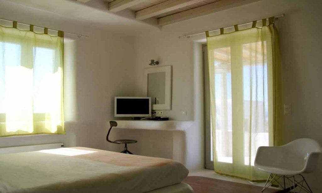 simply designed room with green curtains and a comfortable bed