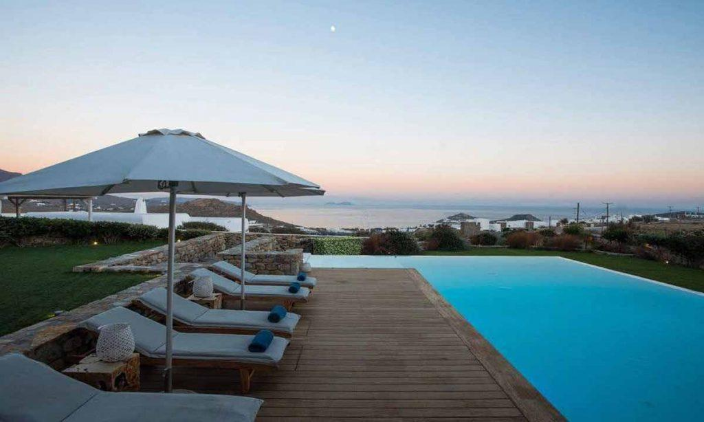 swimming pool area with sunbeds and beautiful view of sunset and sea