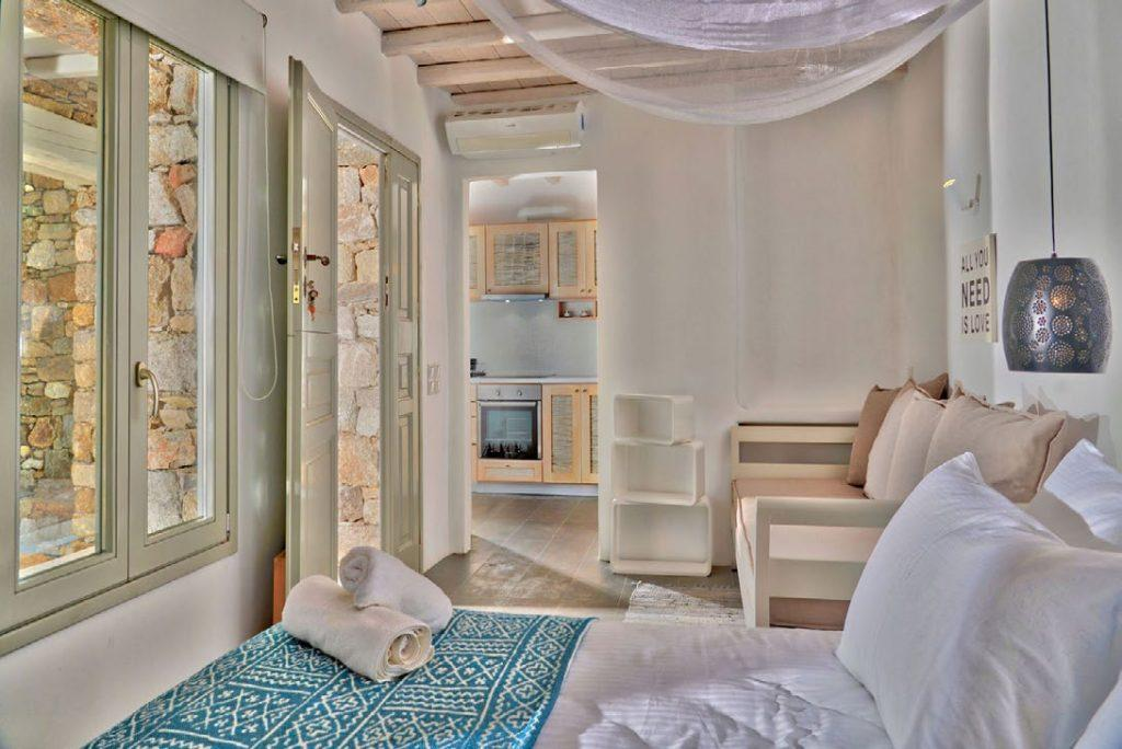 Villa Umabel, Agios Stefanos, Mykonos, Flatscreen TV, Windows, Door, Outside view, Towels, Stone wall, Pillows, Bed, Kitchen, Sleeping room