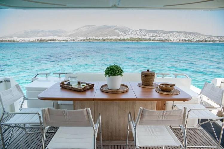 Yacht_Ananas_09.jpg Mykonos Outdoor Dining area, table, chairs, flowers, vase, sea, sky, hill