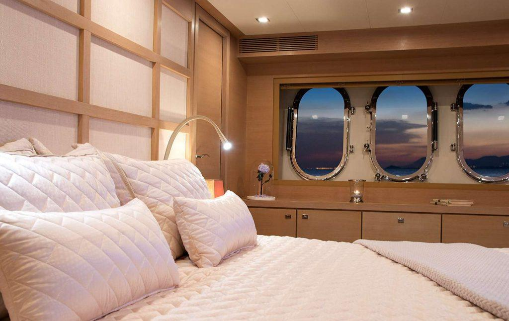 bedroom with white bed with view on sunset throuh round windows