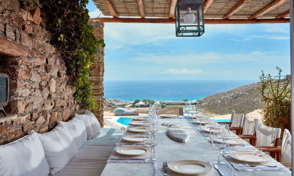 Villa Maksim Agrari Mykonos, outdoor dining area, bench, pillows, chairs, plates, glasses, forks, knives, sea