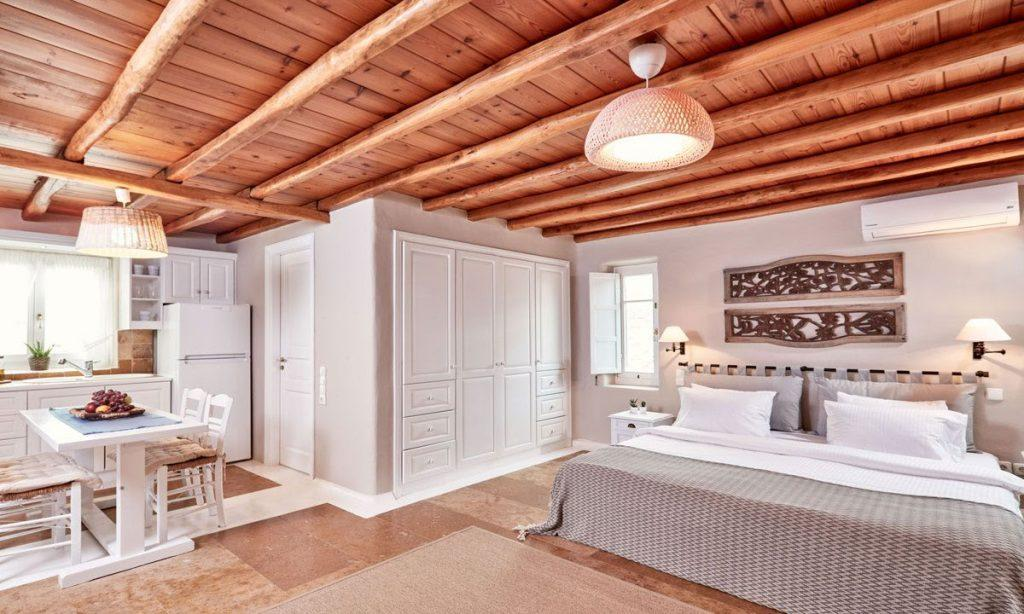 Villa Maksim Agrari Mykonos, 2nd bedroom, king size bed, AC, pillows, nightstand, closet, dining table, chairs, fridge, sink, kitchen, window