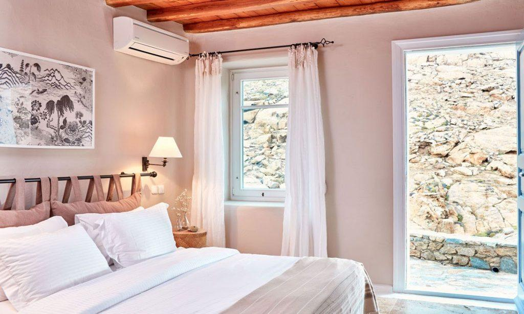 Villa Maksim Agrari Mykonos, 1st bedroom, AC, king size bed, pillows, lamp, nightstand, painting, curtains