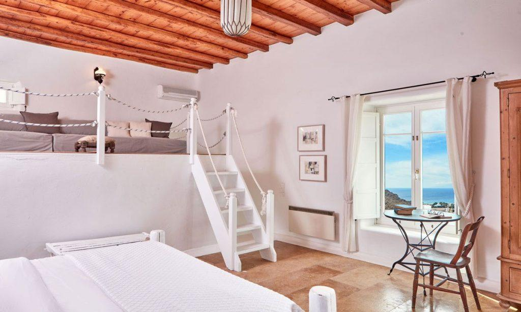Villa Maksim Agrari Mykonos, 5th bedroom, king size bed, stairs, paintings, window, curtains, table, chairs, books, window, AC