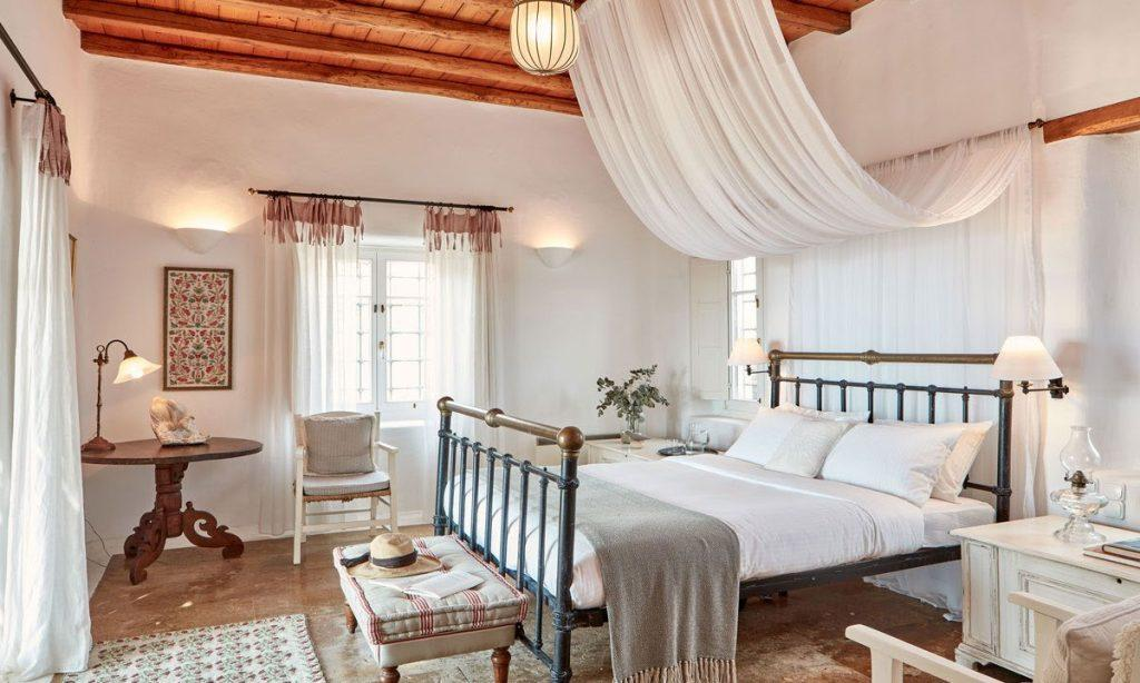 Villa Maksim Agrari Mykonos, 3rd bedroom, king size bed, pillows, curtains, nightstands, hat, table, chair, painting
