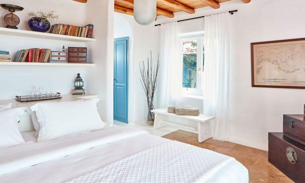 Villa Maksim Agrari Mykonos, 4th bedroom, king size bed, baskets, pillows, panting, shelves, books, flowers, curtains, window
