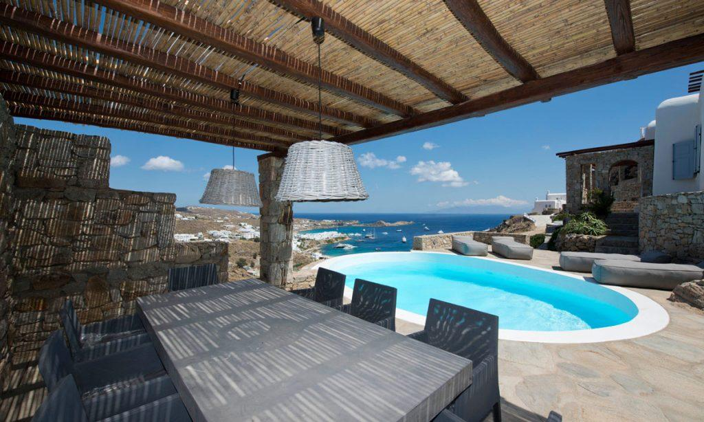 Villa Naenia Psarrou Mykonos, outdoor, pool, dining table, stone wall, villa exterior, sun beds, sea, sky, clouds, boats, island