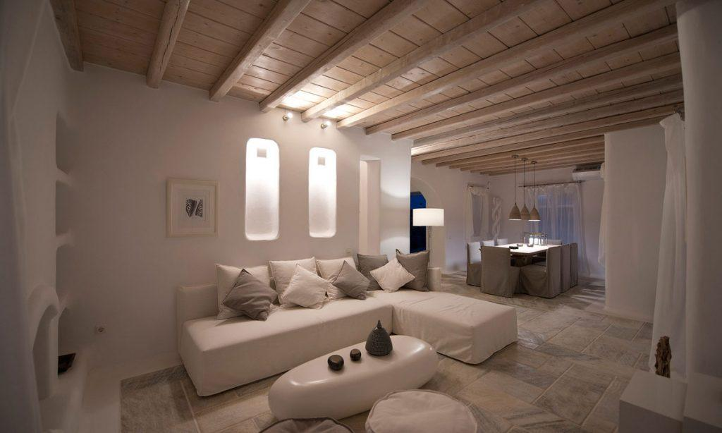 Villa Naenia Psarrou Mykonos, living room, sofa, pillows, table, painting, curtain, fireplace, shelves