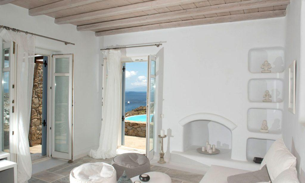 Villa Naenia Psarrou Mykonos, living room, fireplace, candles, shelves, curtains, table, sofa, pillows