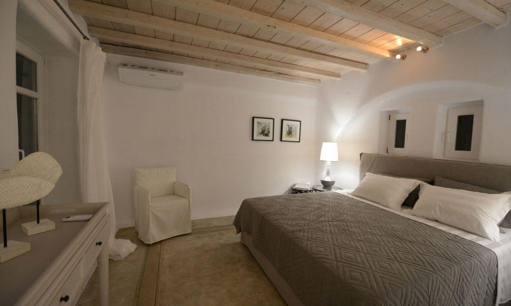 Villa Naenia Psarrou Mykonos, 1st bedroom, king size bed, pillows, windows, paintings, lamp, nightstand, armchair, AC, curtain