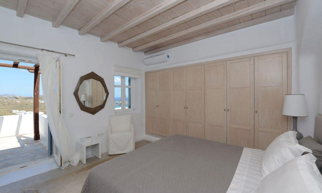 Villa Naenia Psarrou Mykonos, 3rd bedroom, king size bed, lamp, closet, mirror ,curtain, armchair, AC