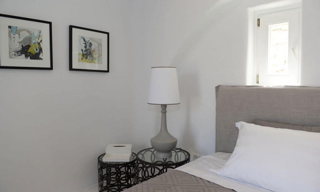 Villa Naenia Psarrou Mykonos, 1st bedroom, king size bed, pillows, nightstand, lamp, paintings, window