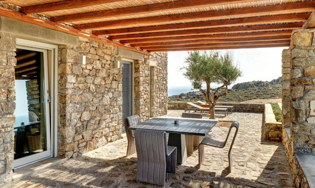 Villa Raisa Super Paradise Mykonos, outdoor, dining table, chairs, tree, stone walls, sea