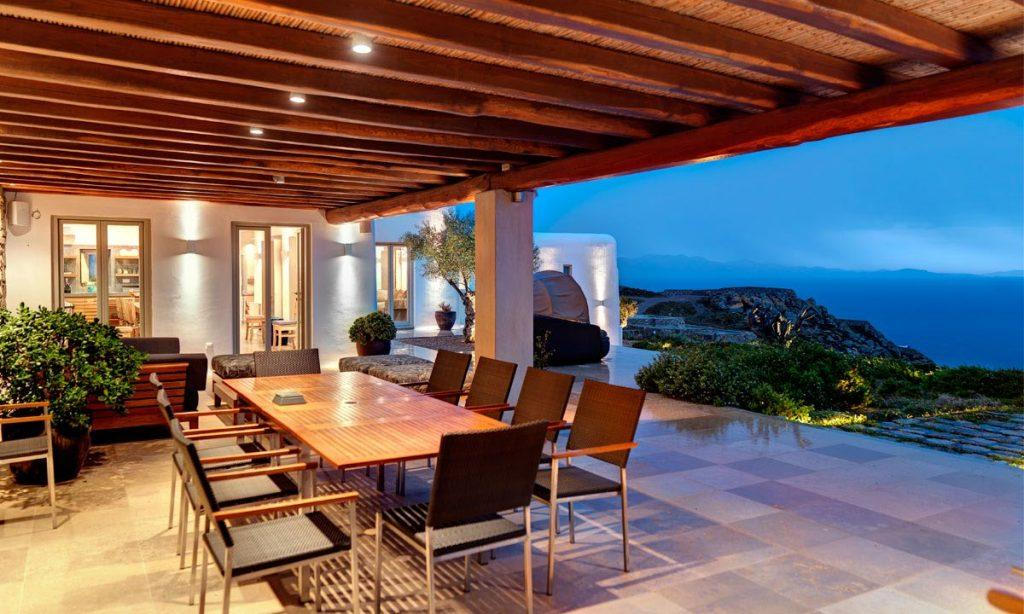 Villa Raisa Super Paradise Mykonos, outdoor dining area, dining table, chairs, plants, sea, sky, lights, night
