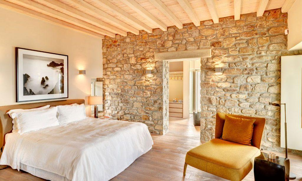 Villa Raisa Super Paradise Mykonos, 1st bedroom, king size bed, painting, armchair, stone wall, pillows, blanket, nightstand, lamp