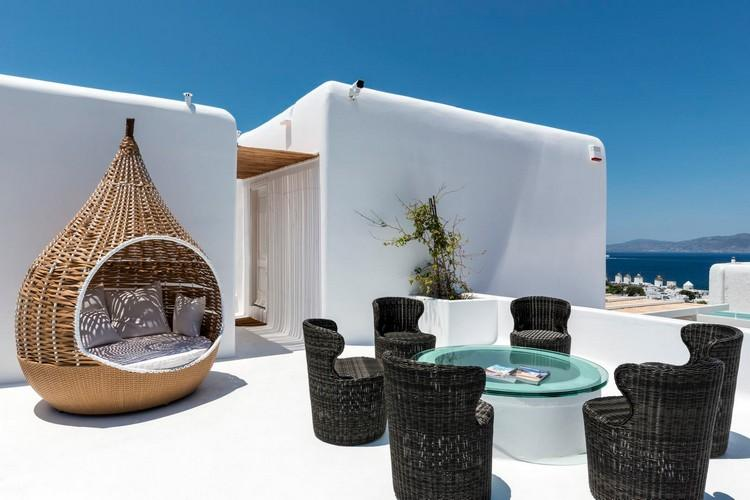 outdoor area with beautiful soft bed and black chairs