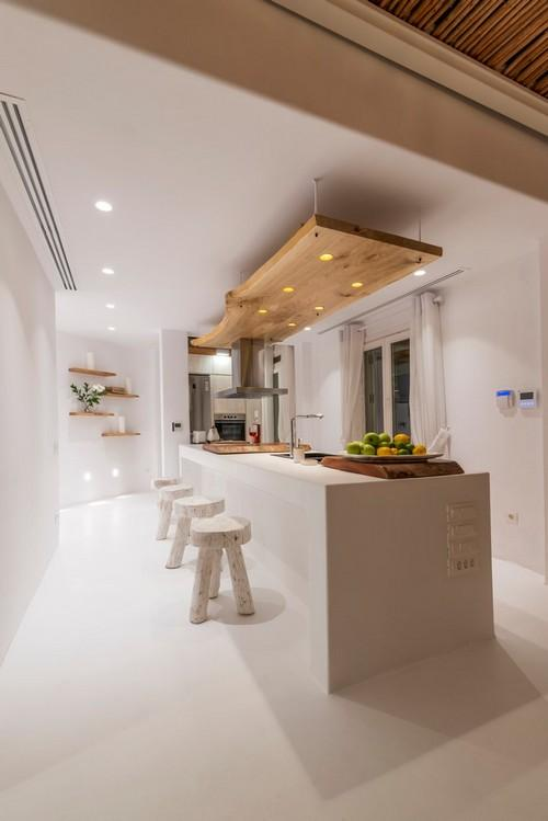 modern designed kitchen with wooden bar chairs and wall lamps